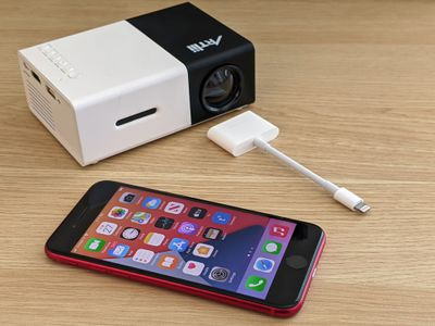 An iPhone with a mini projector and an HDMI adapter.