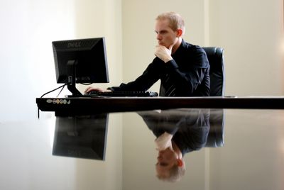Man working at computer keyboard on reflective desk
