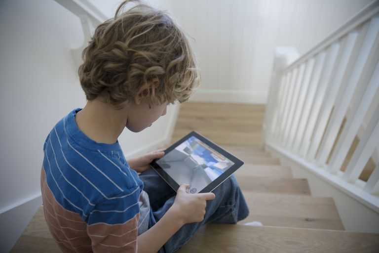 Kid playing game on tablet