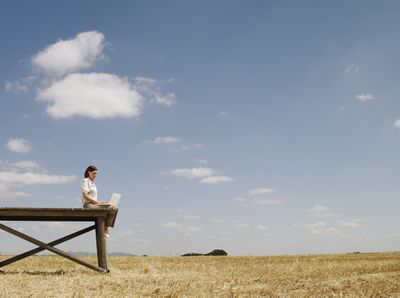 Someone using a laptop on a wooden dock in the middle of a rural field.