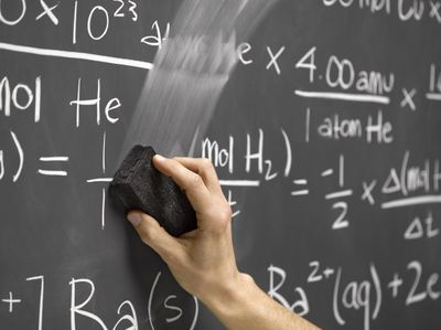 Photo of someone erasing equations written on a chaulkboard