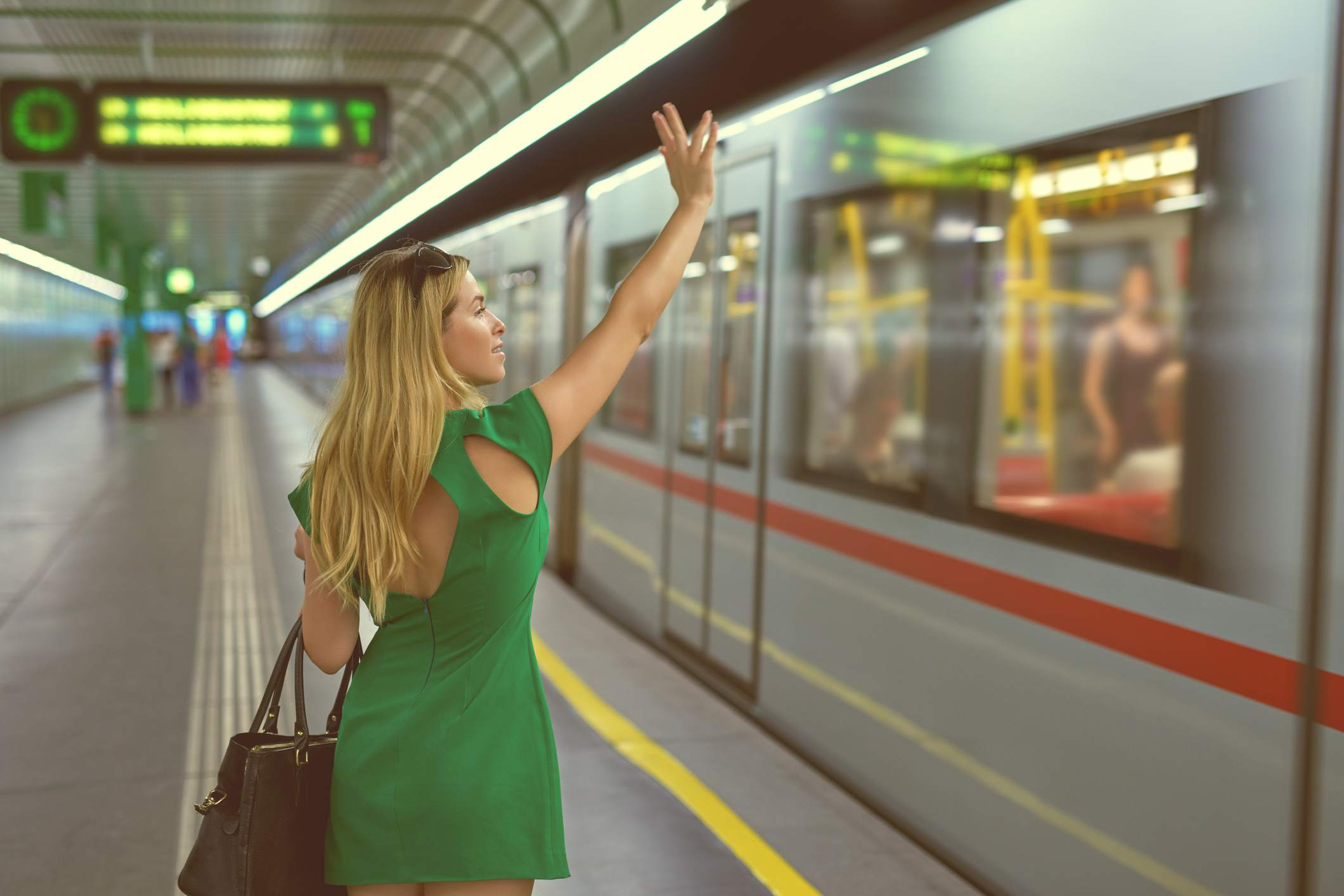 Woman waving to train at station