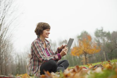 A woman sitting in the leaves downloading fall wallpaper on her tablet