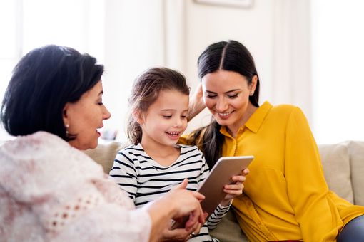 Grandmother, mother, young daughter looking at 7 inch tablet