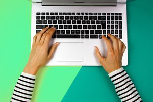Cropped hands of woman using laptop over colored background