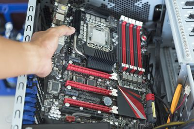 Holding a motherboard in an open computer case.