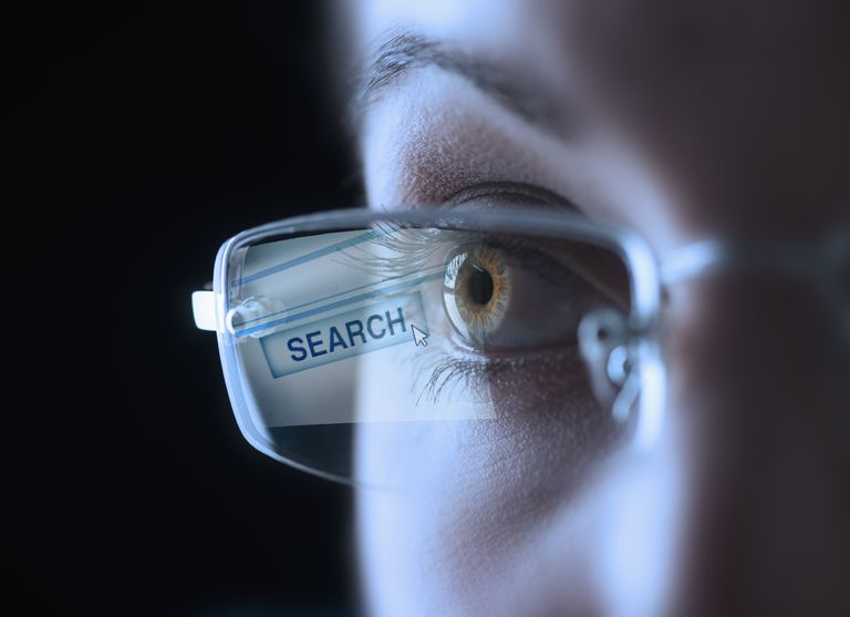 Search button reflected in the glasses of a woman