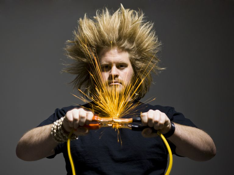 Car battery sparking over jumper cables and electrocuting a man's hair in an artistic interpretation.