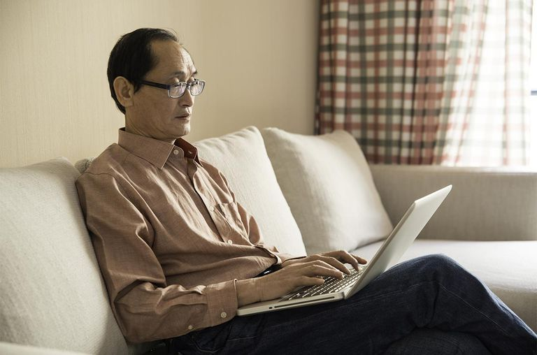 Senior man using laptop sitting on couch