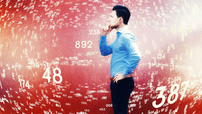 A man standing next to a wall of numbers are varying amounts and sizes