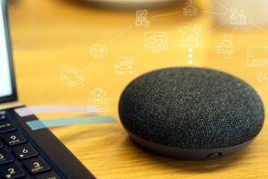 A black Google Home Mini sitting next to a laptop.