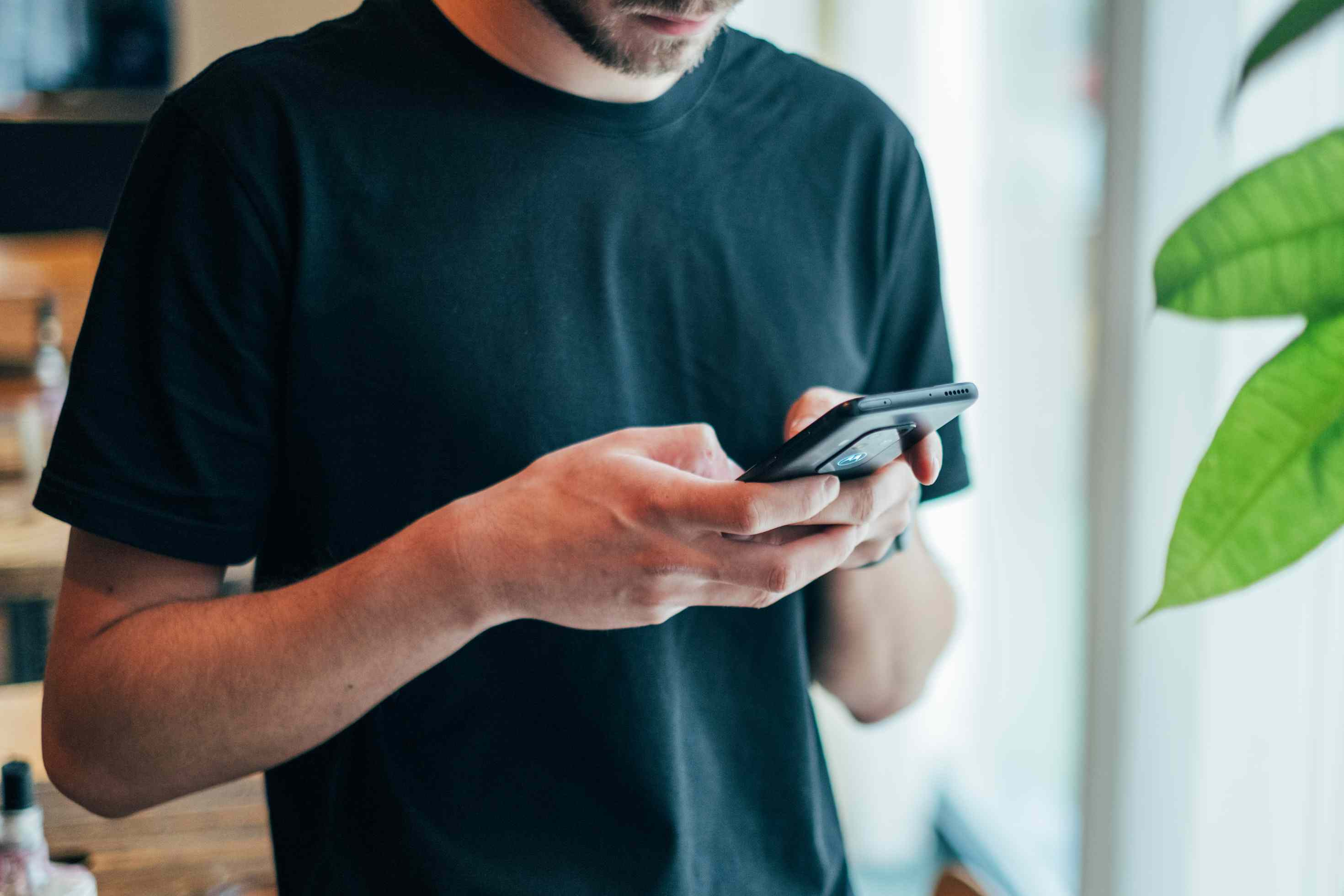 man in black shirt using smartphone