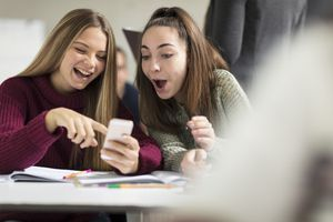 Two young women looking at a smartphone and laughing