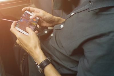 Midsection of a person playing a game on an iPhone