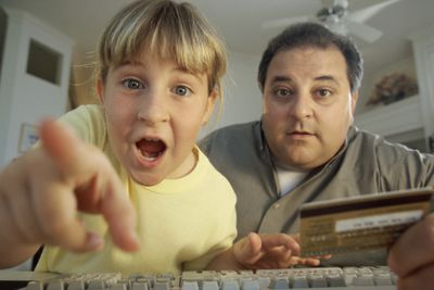 Father and child looking at computer screen with credit card handy