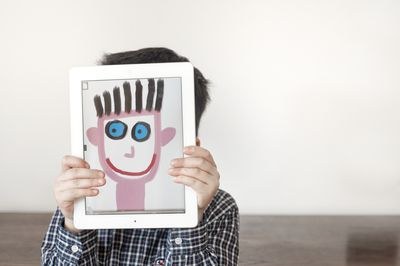 Photo of young boy holding tablet in front of his face with image of painted face.