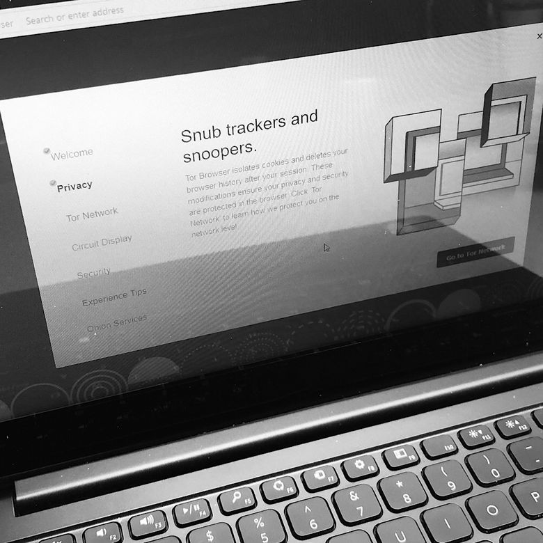 """Black and White photo of a laptop with the TOR Browser open to an explanatory Privacy screen that says """"Snub trackers and snoopers."""""""