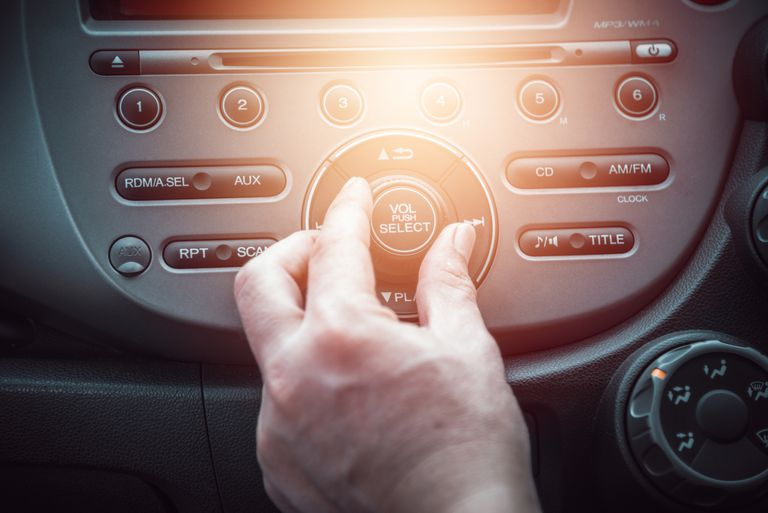 A hand adjusts the volume on a car radio.