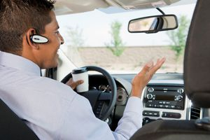 Sales rep driving car holding a cup of coffee talking on a Bluetooth headset