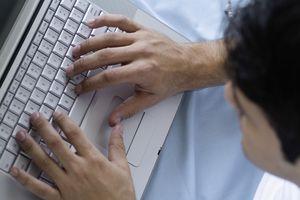 Teenage boy typing on laptop, close-up