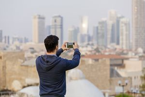 Man in blue sweatshirt overlooking a city taking a photo on his phone