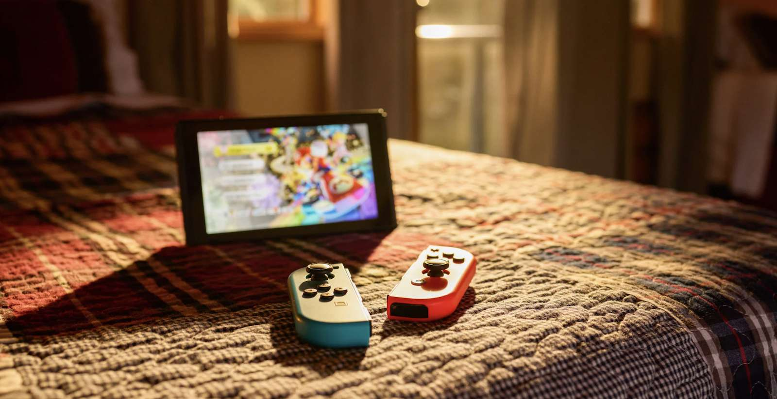 Nintendo Switch w/ kickstand and Joy-Con controllers resting on a bed