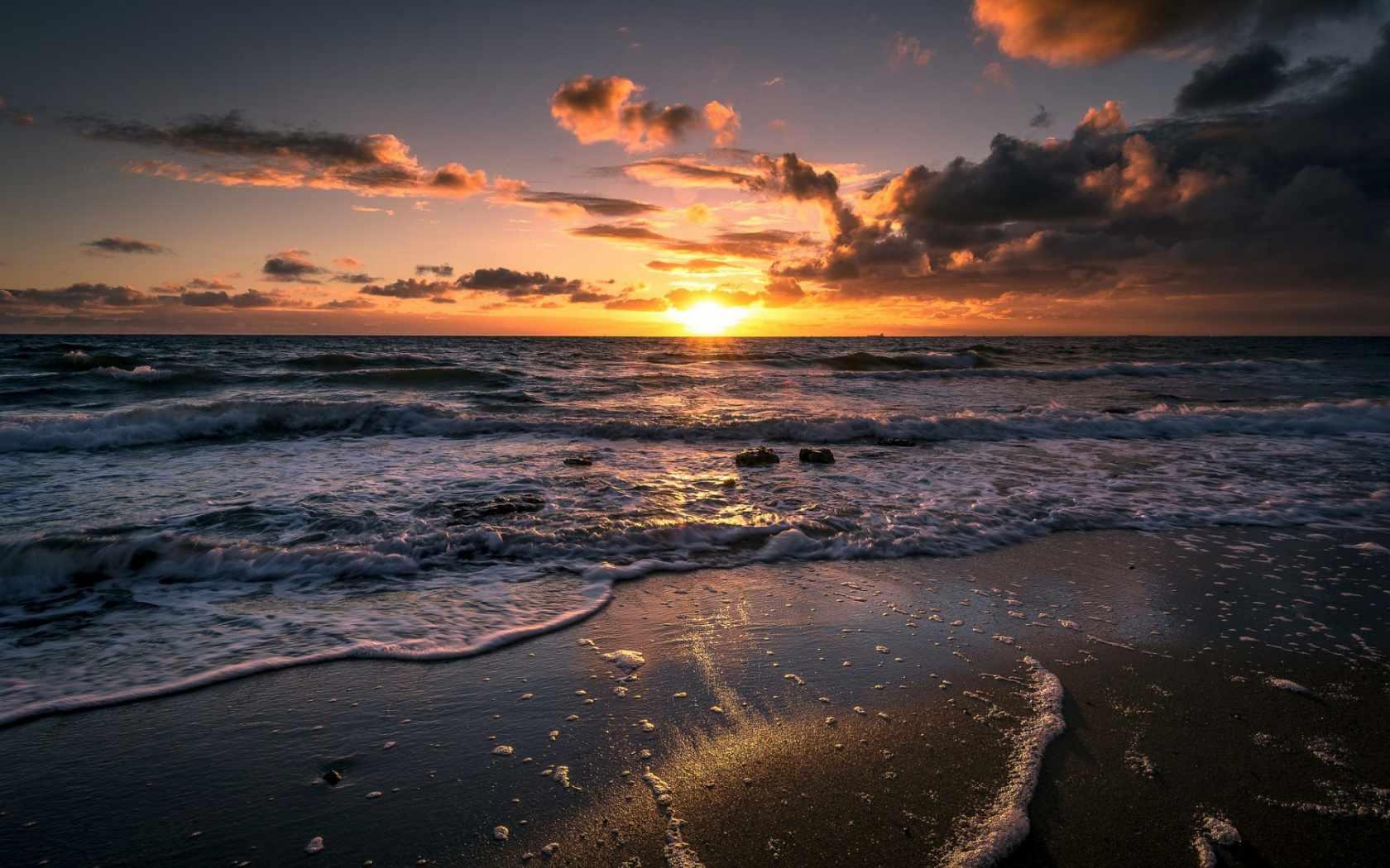Free ocean wallpaper featuring a beach view of a sunrise over foamy ocean