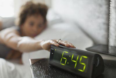 Woman hitting button on alarm clock