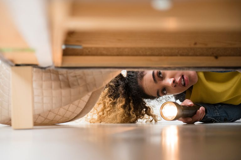 Mixed Race woman looking under bed with flashlight