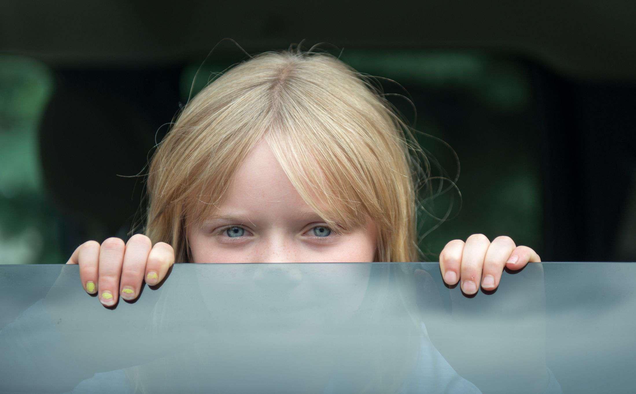 Little girl looking through a car window.