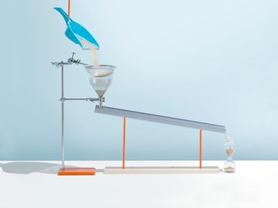 Based on the Rube Goldberg machines where simple tasks are made complicated