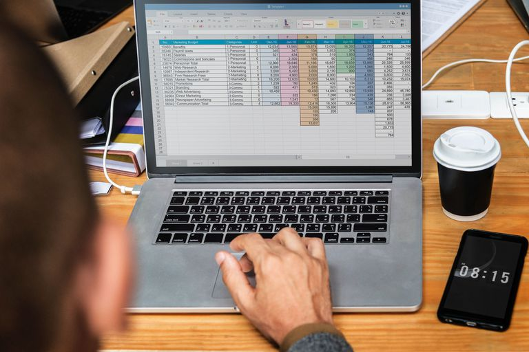 Man working on laptop with excel spreadsheet open Excel