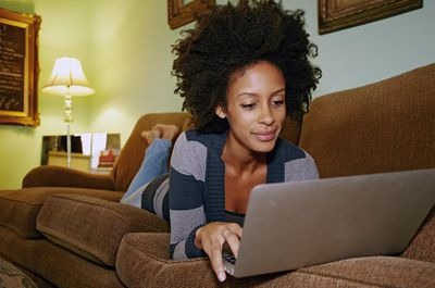 Person using laptop on sofa