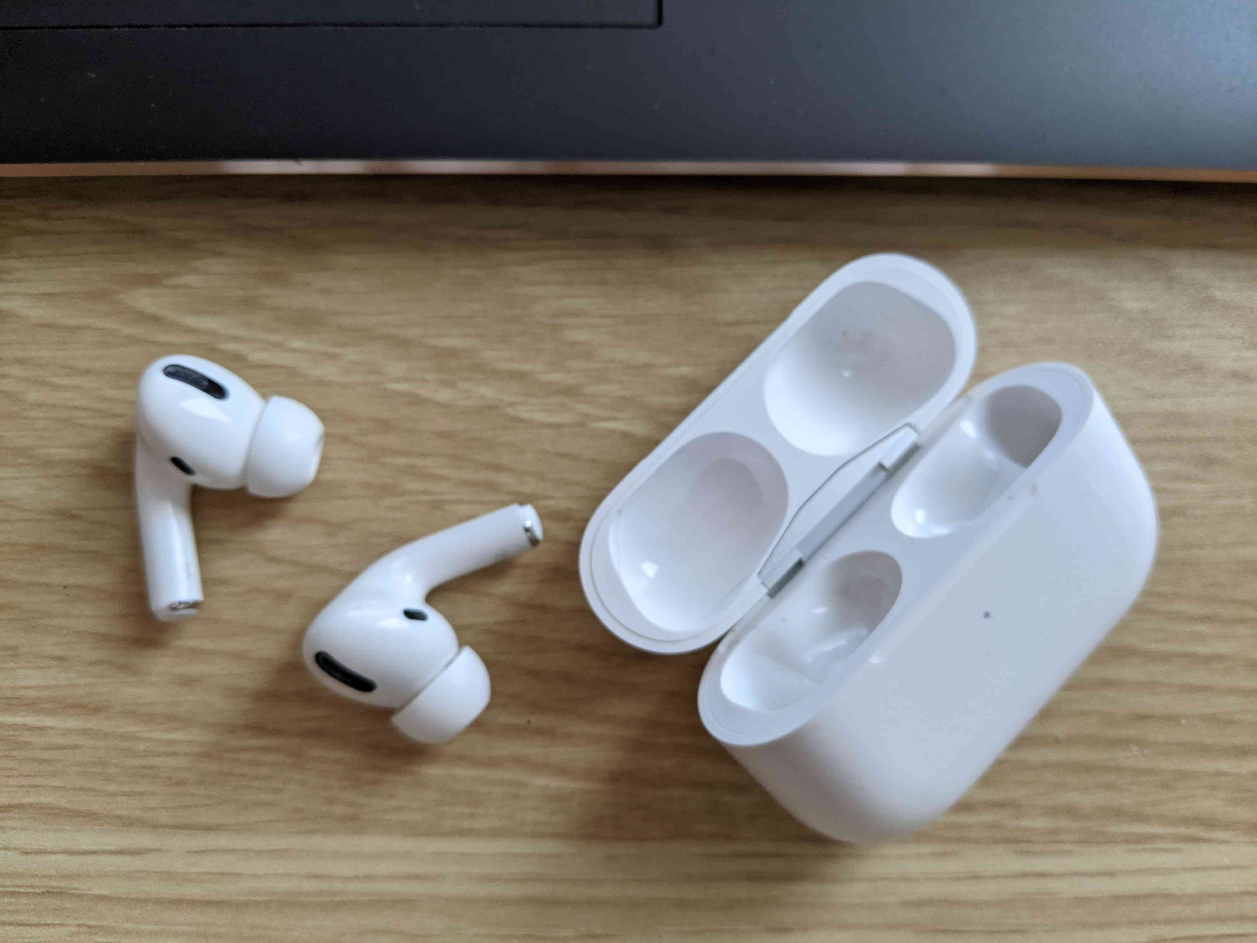 AirPods Pro removed from their case next to an HP laptop.