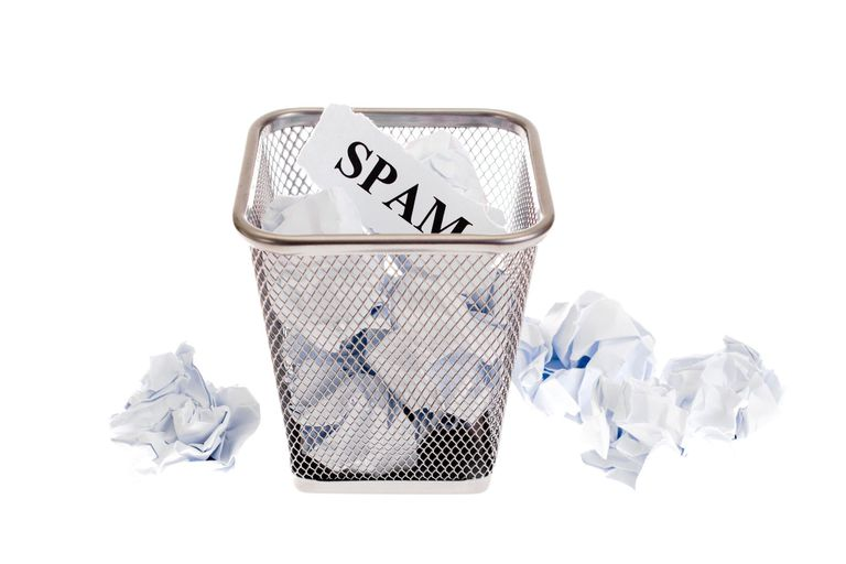 waste basket filled with crumpled paper. One piece says SPAM on it