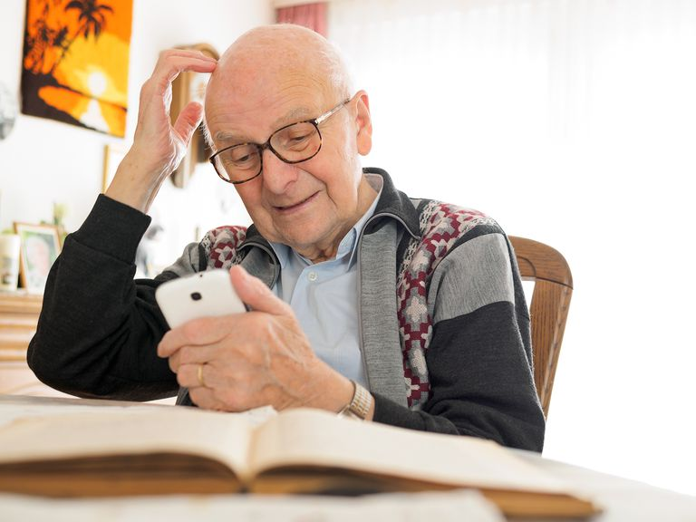 Elderly man sitting at table using cell phone rubbing his head