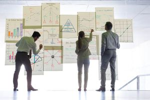 Business people working with charts and graphs on glass wall