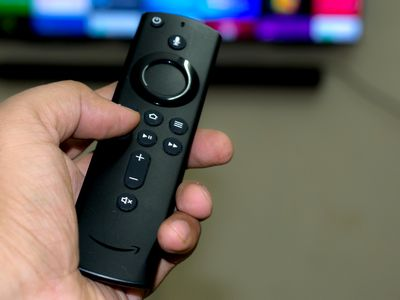A man's hand holding an Amazon Firestick remote controller.