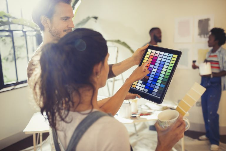 A photo of a man and woman looking at paint samples on a tablet.