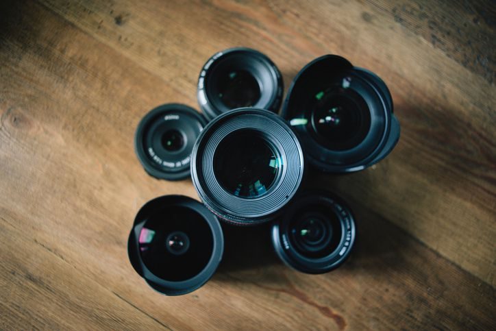 Camera lenses arranged on a wooden table
