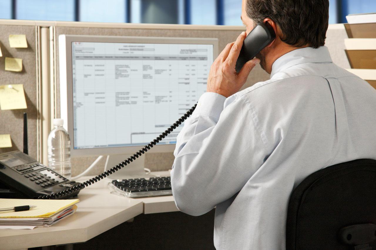 Man talking on phone in an office.