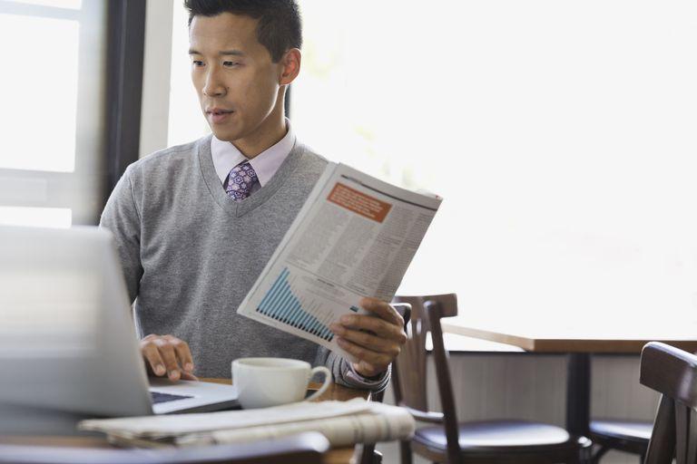 Man holding magazine working on computer