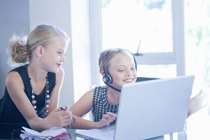 Kids using a laptop with one using a headset