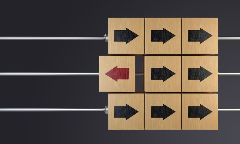 Standing Out From The Crowd With Wooden Cubes arrows facing in one direction and one in a different direction