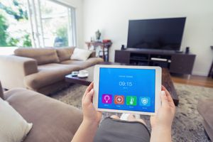 Homeowner sitting on cough using smart app to control air conditioner.