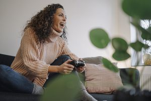 A woman smiling and laughing while holding a PlayStation controller