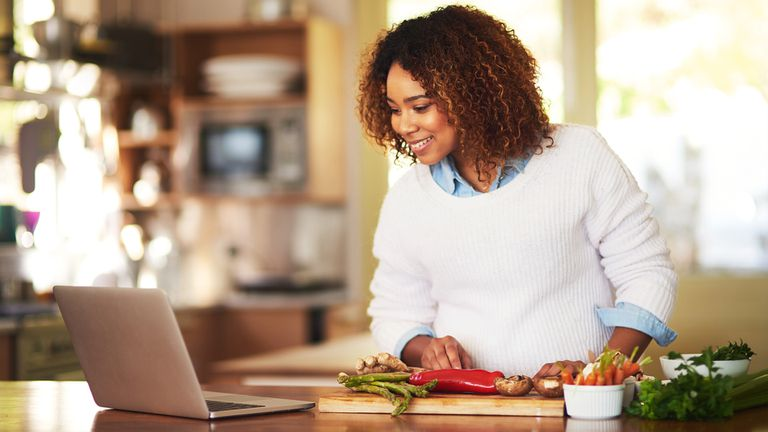 Woman in her kitchen cooking while looking at a Windows 10 app
