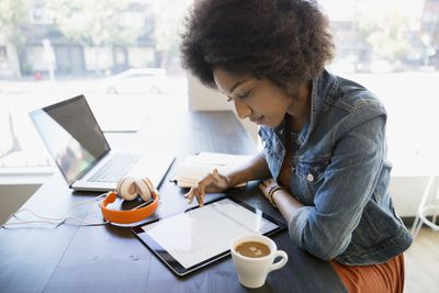 Woman using iPad and computer at coffee shop