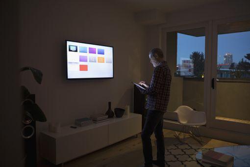 Senior man using smart TV apps on digital tablet in dark living room
