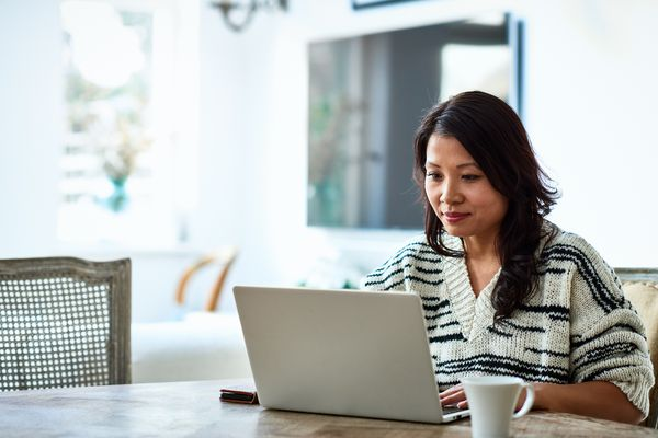 A woman sitting at a table looking at a laptop with a cup of coffee next to her